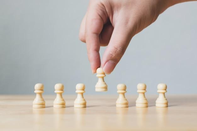 Mano elige un ajedrez de madera destacándose entre la multitud
