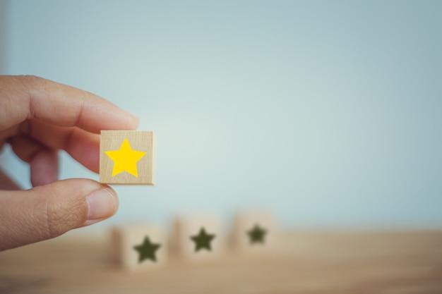 Mano elige forma de estrella amarilla de madera en la mesa