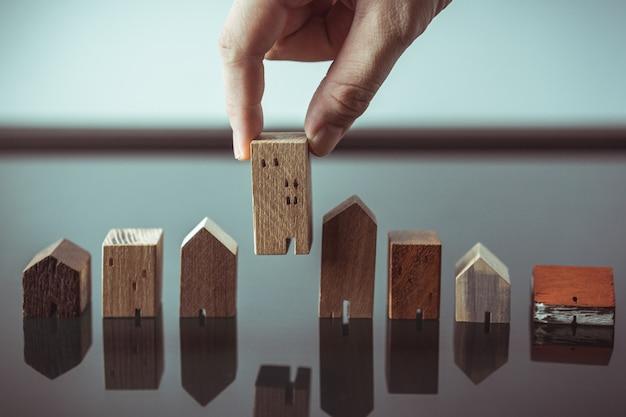 Mano eligiendo el modelo de mini casa de madera del modelo y la fila de monedas en la mesa de madera