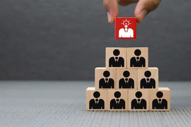 Mano elija icono de empresario en bloque de madera.