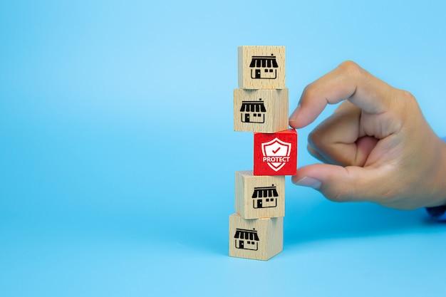 Mano elija el icono de seguro con la tienda de iconos de marketing de franquicia en el blog de juguetes de madera de cubo está apilado. conceptos gestión de riesgos y estructuras financieras estables.