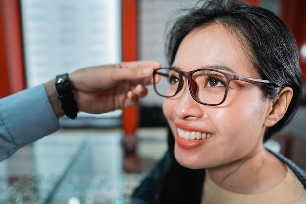 La mano de un empleado está ayudando a ponerse un par de anteojos que una mujer que se ha realizado un examen de la vista ha elegido en una clínica oftalmológica