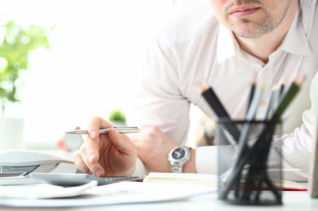 Mano de empleado masculino sostener bolígrafo plateado usando calculadora