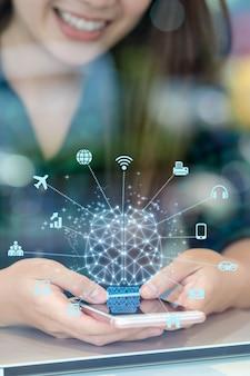 Mano de empresaria asiática de primer plano usando el móvil con cerebro poligonal