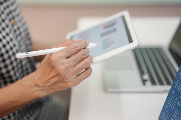 Mano de empresaria de gerente senior con punta de lápiz en el dispositivo de tableta de pantalla de tablero