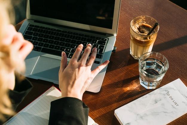 Mano de la empresaria que trabaja en la computadora portátil con un vaso de batido de chocolate y agua en el escritorio de madera