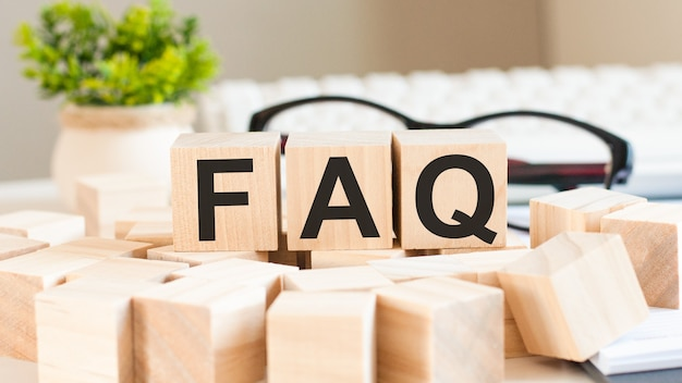 Mano de empresaria sosteniendo la palabra faq con bloque de cubo de madera.