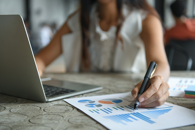 La mano de una empresaria está sosteniendo una pluma que señala en el gráfico y está usando una computadora portátil.