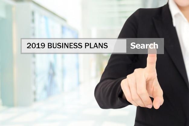 Mano empresaria tocando planes de negocio 2019 en la barra de búsqueda