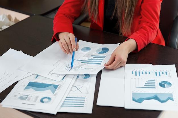 Mano de empresaria trabajando con gráfico de negocio o tabla de análisis. cerrar el concepto de estrategia y análisis de equipo de negocios.