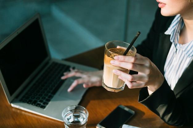 Mano de empresaria usando laptop y sosteniendo vaso de batido de chocolate