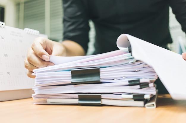 Mano del empresario para buscar información en pilas de papel en la oficina de escritorio.