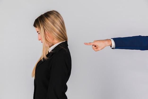La mano de un empresario culpando a la joven empresaria contra el fondo gris.