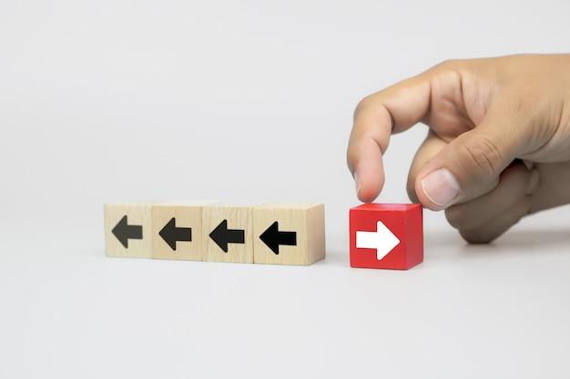 La mano del empresario elige un blog de juguetes de madera de cubo con iconos de punta de flecha apuntando en direcciones opuestas