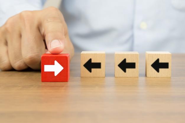 La mano del empresario elige un blog de juguetes de madera de cubo con iconos de punta de flecha que apuntan a direcciones opuestas para el cambio empresarial