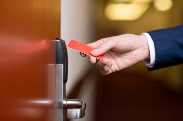 Mano del empresario moderno sosteniendo una tarjeta de plástico roja por la puerta de madera cerrada de la habitación del hotel para entrar