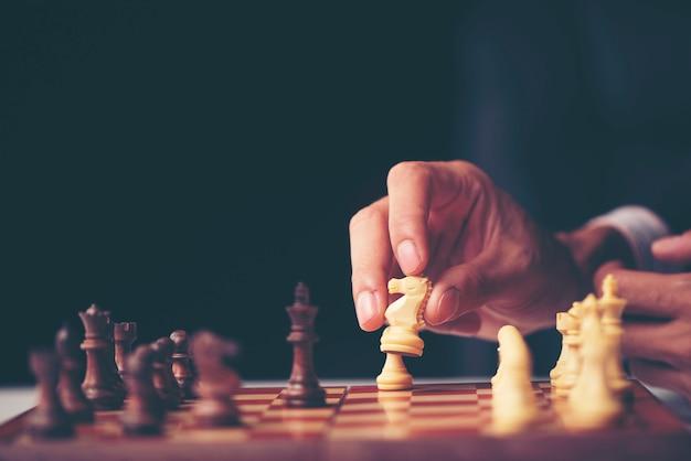 Mano de empresario moviendo figura de ajedrez