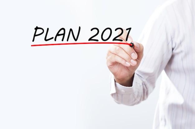 Mano de empresario plan de escritura 2021 con marcador rojo en tablero de paño transparente, concepto de negocio