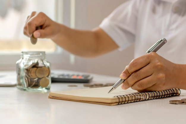 La mano de un empresario que está escribiendo notas en un cuaderno, incluido el ahorro de dinero, idea de hacer información financiera en casa.