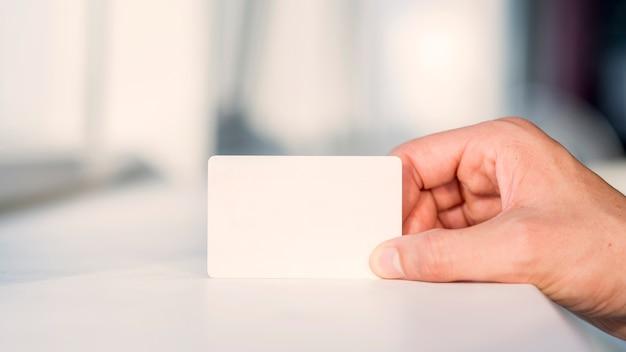 Mano del empresario que sostiene la tarjeta blanca en blanco