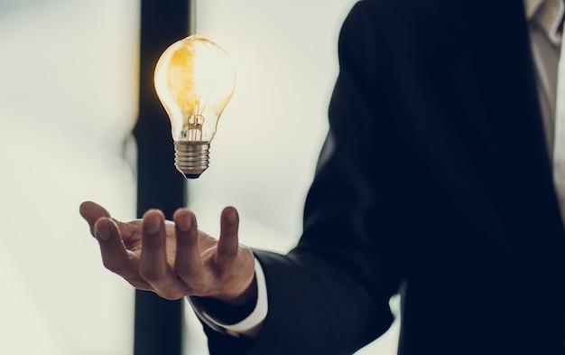 Mano del empresario sosteniendo la bombilla como símbolo de la idea de éxito, concepto de inspiración de innovación