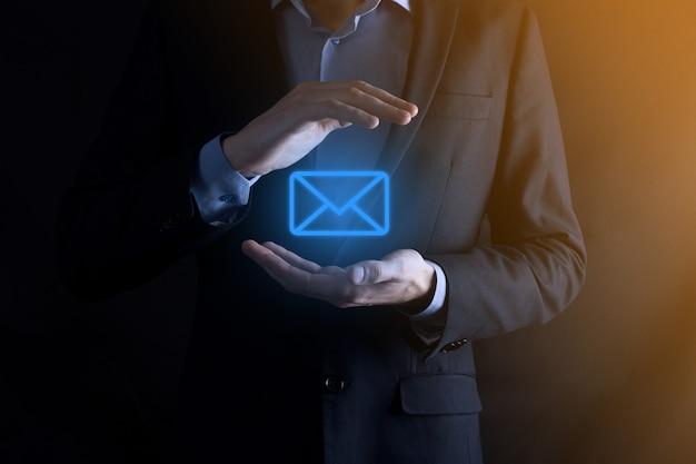 Mano de empresario sosteniendo el icono de correo electrónico, contáctenos por correo electrónico del boletín y proteja su información personal del correo no deseado. centro de llamadas de servicio al cliente en contacto con nosotros concepto.