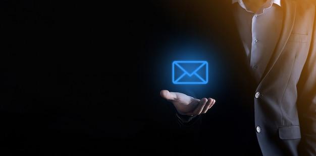 Mano de empresario sosteniendo el icono de correo electrónico, contáctenos por correo electrónico del boletín y proteja su información personal