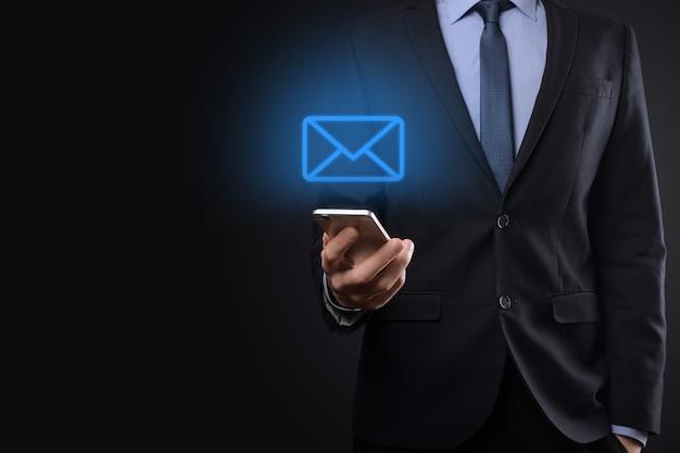 Mano de empresario sosteniendo el icono de correo electrónico, contáctenos por correo electrónico del boletín