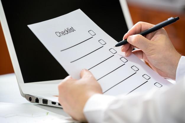 Mano de un empresario sosteniendo una pluma y comprobando la lista de verificación.