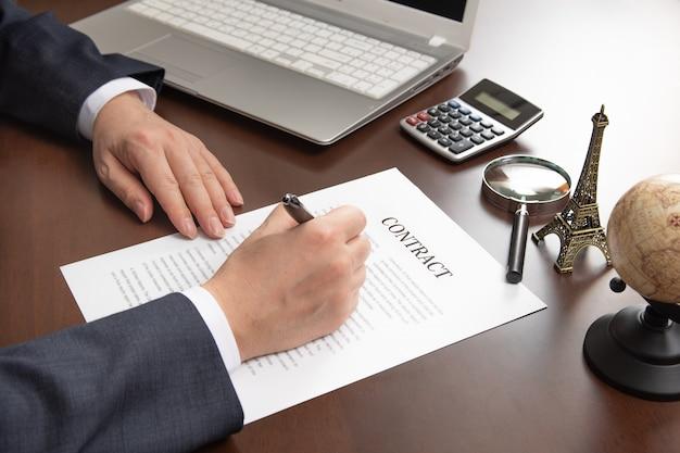 Mano del empresario sosteniendo la pluma en la mano y firmando el documento del contrato.