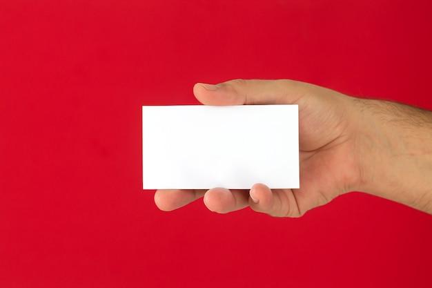 Mano de empresario sosteniendo la tarjeta de presentación en blanco sobre fondo rojo.
