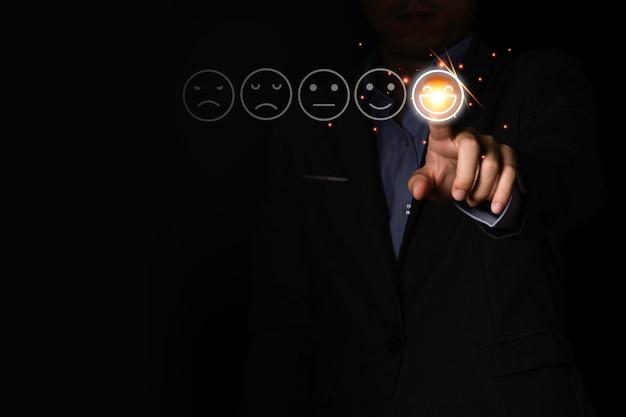 Mano de empresario tocar icono de humor de emoción de sonrisa sobre fondo negro. es una encuesta de satisfacción del mercado y servicio al cliente.