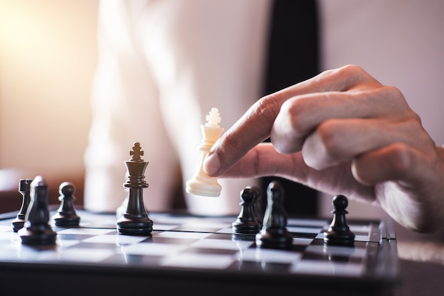 Mano del empresario uso pieza de ajedrez rey juego de juego blanco para análisis de desarrollo nuevo st