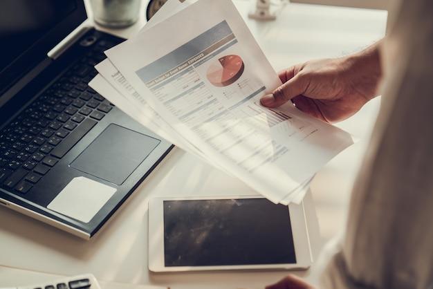 Mano de empresarios calculando intereses, impuestos y ganancias para invertir en bienes raíces y compra de vivienda