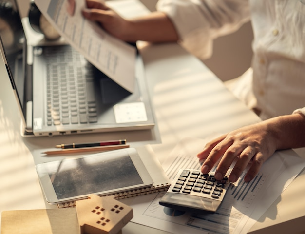 Mano de empresarios que calculan intereses, impuestos y ganancias para invertir en bienes raíces y compra de vivienda