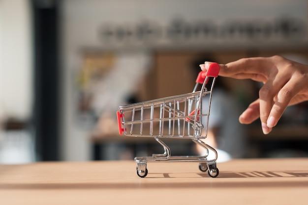 Mano empujando un carrito de compras pequeño