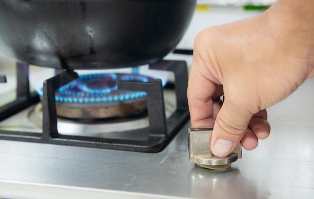 Mano encendiendo el quemador para cocinar en la cocina