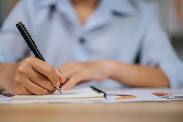 La mano de enfoque selectivo de una mujer joven asiática en anteojos usa bolígrafo trabajando con papeles en la oficina en casa, durante la cuarentena covid-19 autoaislamiento en casa, trabaja desde el concepto de hogar