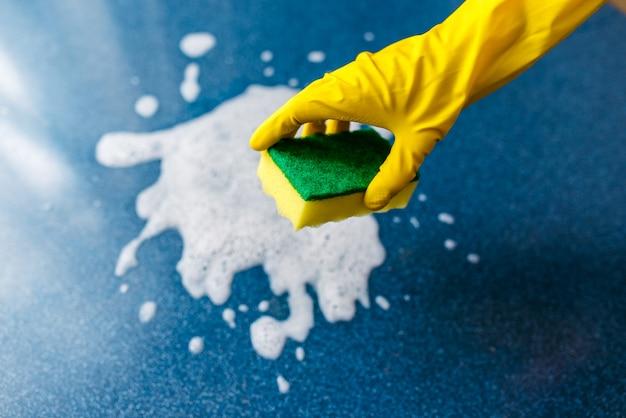 Una mano enguantada limpia espuma y suciedad con una toallita. limpieza.