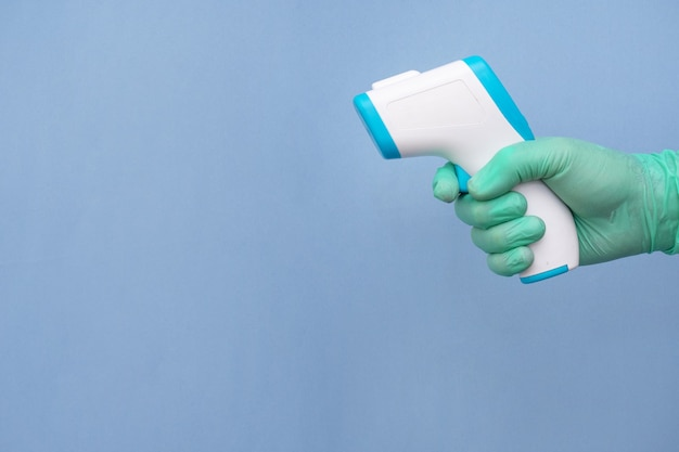 Mano enguantada de un trabajador de la salud sosteniendo un termómetro aislado en azul