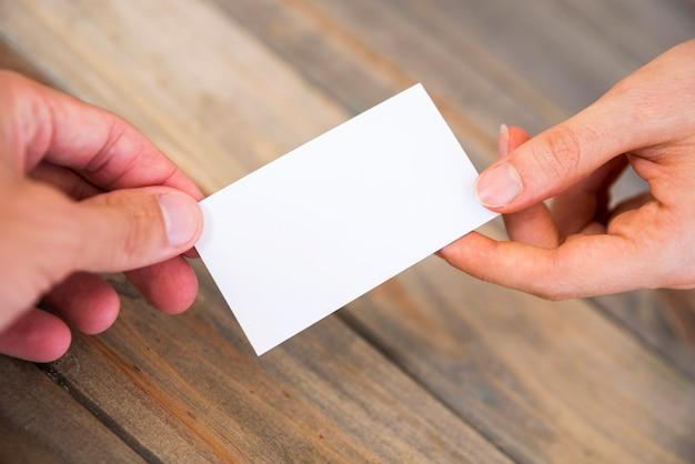 Mano enseñando una tarjeta de visita en blanco