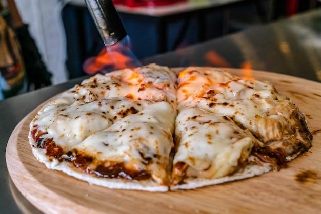 La mano es el queso de la antorcha para la comida en el restaurante.