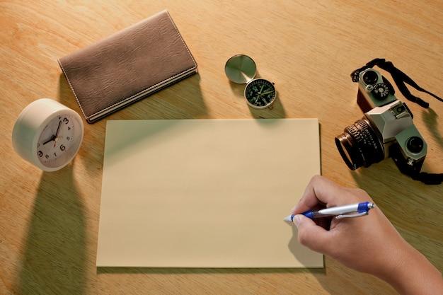 Mano escribiendo algo en la hoja de papel.