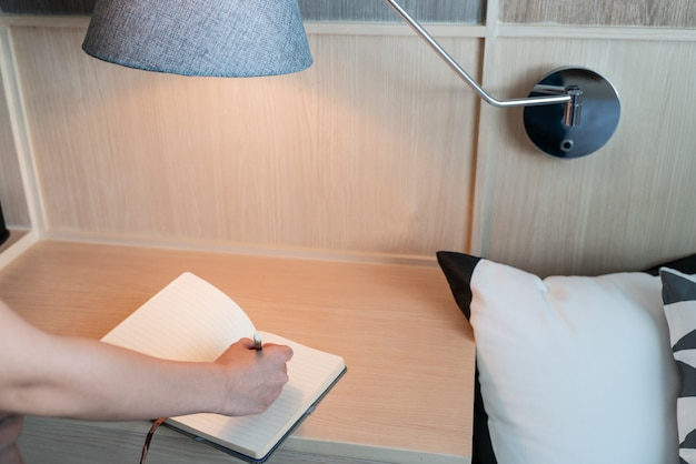 Mano escribiendo en el cuaderno en el escritorio con lámpara
