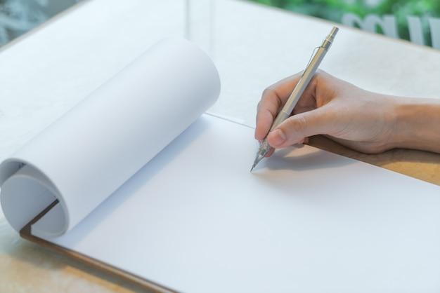 Mano escribiendo en una libreta