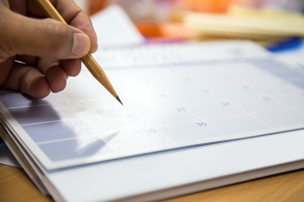 Mano escribiendo un memo de mensaje de nota en el calendario.