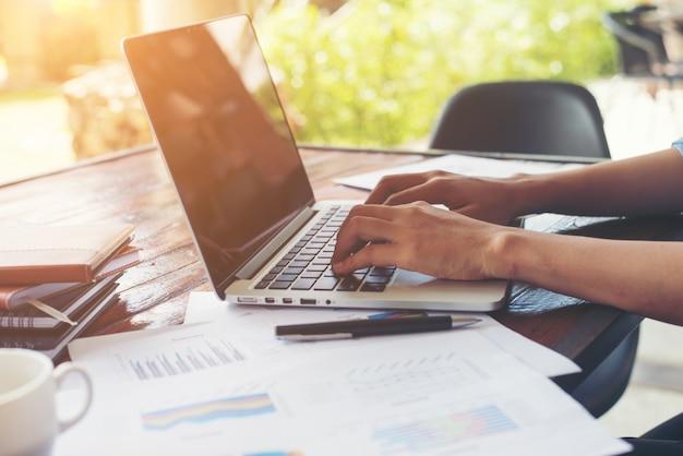 Mano escribiendo mujer de negocios en el teclado portátil con cha financiera Foto gratis
