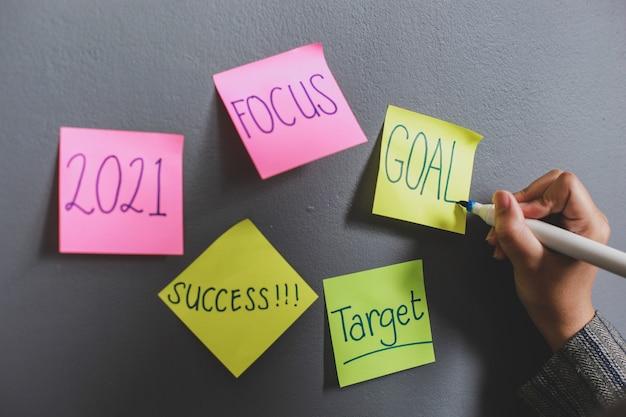 Mano escribiendo objetivos 2021 en notas adhesivas en la pared de la oficina