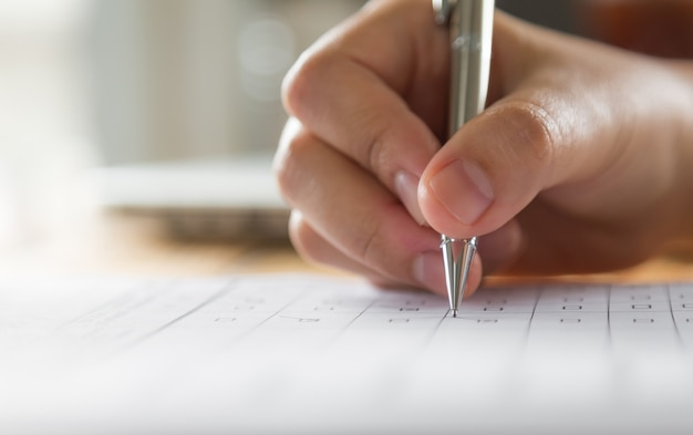 Mano escribiendo en un papel con un bolígrafo