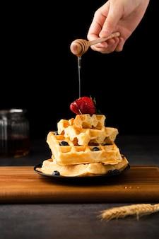 Mano esparciendo miel sobre waffles con frutas